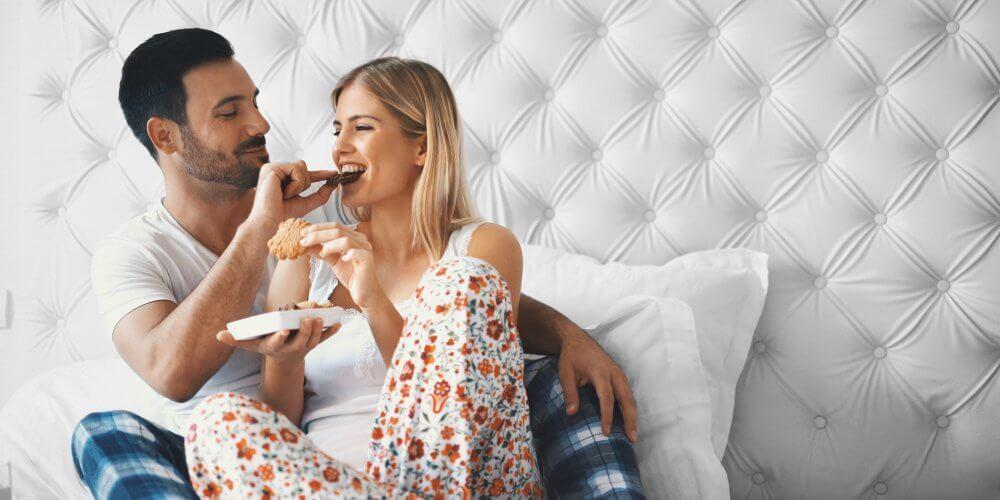 couple mangeant dans un lit