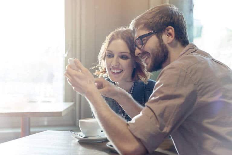 couple au café regardant un téléphone